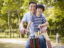 Asian father and son enjoying biking outdoors. Asian father and elementary-age son enjoying riding a bike outdoors in a park Royalty Free Stock Images