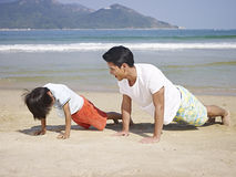 Asian father and son exercising on beach stock photography