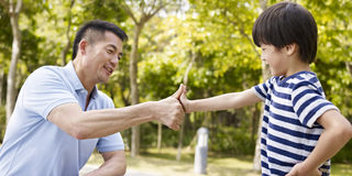 Asian father and son making a deal. Asian father and elementary-age son sealing a deal or promise outdoors in a park Royalty Free Stock Photography
