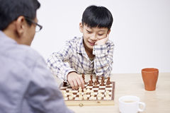 Asian father and son playing chess Stock Photography
