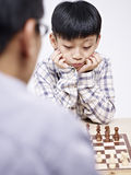 Asian father and son playing chess Royalty Free Stock Images