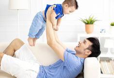 Father And Son Playing On Sofa. Asian Father And Son Playing On Sofa royalty free stock images