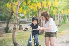 Asian father and son riding bicycle royalty free stock photos