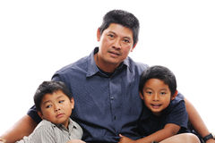Asian Father with sons. Asian father cuddles his two sons Stock Photos