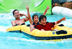 Asian father and sons having fun tubing at a waterpark. Asian Family having fun tubing going through a waterfall in  waterpark Royalty Free Stock Photography