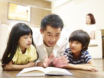 Asian father reading book telling story to two children. Asian father and two children lying on front on floor reading book while mother watching in the Royalty Free Stock Photo