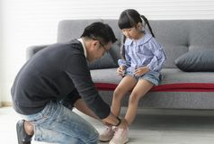 Asian father wear shoes daughter together in livingroom at home.  stock images