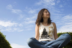 Asian Female. Sitting against blue sky stock images