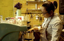 Asian female barista making coffee Royalty Free Stock Photography