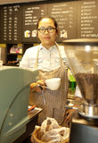 Asian female barista standing behind coffee machine and holding Royalty Free Stock Photos