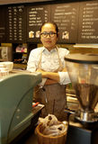 Asian female barista standing behind coffee machine Stock Images