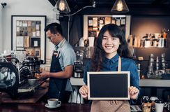 Asian female barista wear jean apron holding blank blackboard coffee menu at counter bar with colleague with smile face ,cafe. Service concept,business owner stock photo
