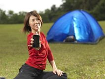 Asian female camper showing her mobile phone Royalty Free Stock Images