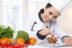 Asian female chef garnishing Royalty Free Stock Photo