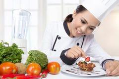 Asian female chef garnishing Royalty Free Stock Photo