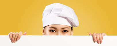 Asian female chef holding poster for the text Royalty Free Stock Image