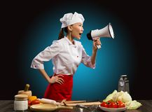 Asian female chef shouting into a megaphone. In front of her kitchen table with vegetables and items Royalty Free Stock Photos