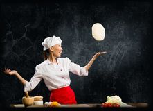 Asian female chef tosses a piece of dough Stock Images
