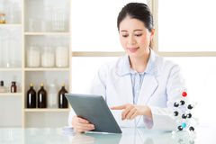 Asian female chemist use notepad to research for future Chemical. Formula and holding molecular model Stock Photography