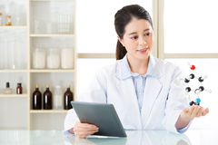 Asian female chemist use notepad to research for future Chemical. Formula and holding molecular model Stock Photos