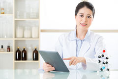 Asian female chemist use notepad to research for future Chemical. Formula and holding molecular model Royalty Free Stock Image