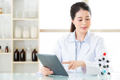 Asian female chemist use notepad to research for future Chemical. Formula and holding molecular model Stock Images