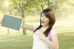 Asian female college student pointing at blank chalkboard Royalty Free Stock Image