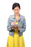 Asian female college student taking down notes Stock Image