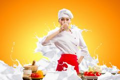 Asian female cook against milk splashes. In red apron against color background drinking milk Stock Image