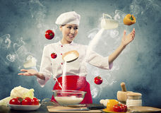 Asian female cooking with magic. Against color background Royalty Free Stock Photos