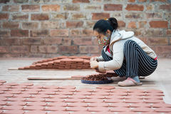 Asian female crafswoman processing ceramic brick Royalty Free Stock Image