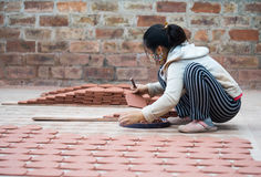 Asian female crafswoman processing ceramic brick Royalty Free Stock Photo