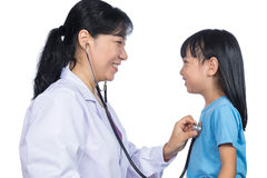 Asian female doctor examining a Chinese little girl by stethosco Stock Images