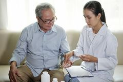 Doctor giving pills to his patient royalty free stock images