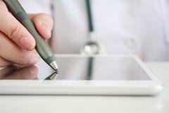 Asian female doctor hand writing digital prescription on tablet Stock Photo