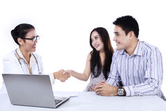 Asian female doctor handshake with pregnant woman - isolated Royalty Free Stock Photos