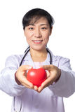 Asian female doctor holding red heart with stethoscope Royalty Free Stock Image