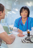 Asian female doctor with patient sitting at table and speaking Royalty Free Stock Photography