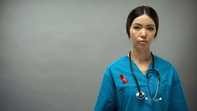 Asian female doctor with red ribbon, international HIV AIDS awareness sign stock photography