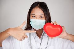 Asian female doctor show OK point to red heart. On gray background royalty free stock image