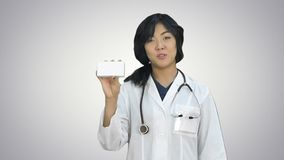Asian female doctor showing a bottle of tablets looking at camera on white background. Close up. Professional shot in HD resolution. 080. You can use it e.g stock video footage