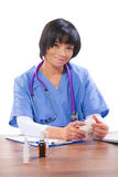 Asian female doctor sitting near the table holding bottle of pil Royalty Free Stock Photography