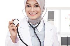 Asian female doctor smiling while using stethoscope Stock Photos