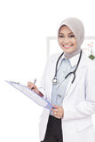 Asian female doctor with stethoscope smiling while writing down Royalty Free Stock Photos