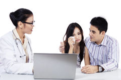 Asian female doctor with a young couple Royalty Free Stock Images