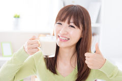 Asian female drinking milk and thumb up Stock Photos