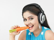 Asian female eating carrot Royalty Free Stock Images