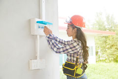 Asian female Electrician or Engineer check or Inspect Electrical system circuit Breaker. Pretty Asian female Electrician or Engineer check or Inspect Electrical Royalty Free Stock Photography