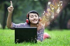 Asian female enjoy music on green field Royalty Free Stock Photos