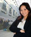 Asian female event organiser. With exhibition in background Royalty Free Stock Photography